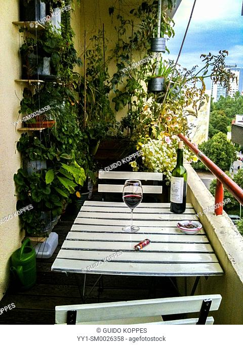 Berlin, Germany. Cozy balcony with plants, table and a glass of wine, an example of Urban Gardening