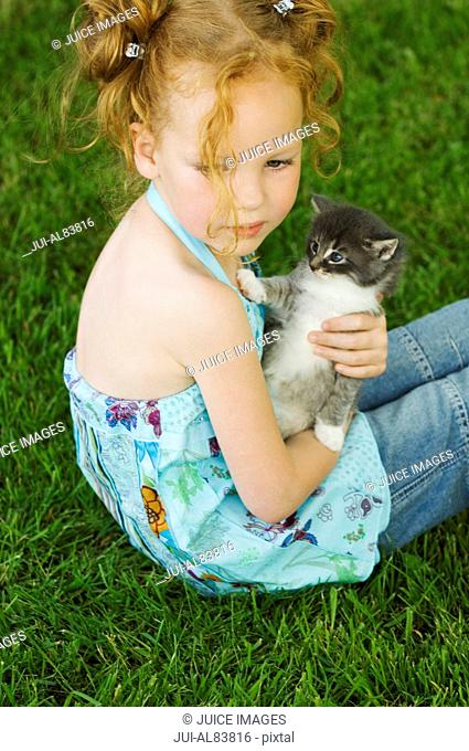 Young girl with kitten in grass