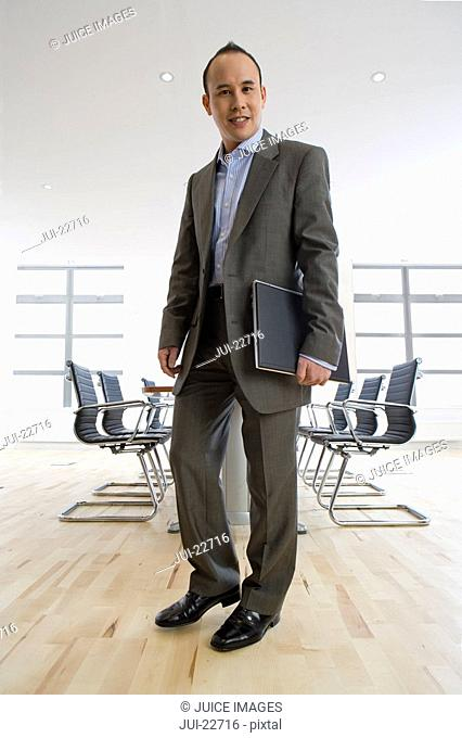 Smiling businessman holding laptop in conference room