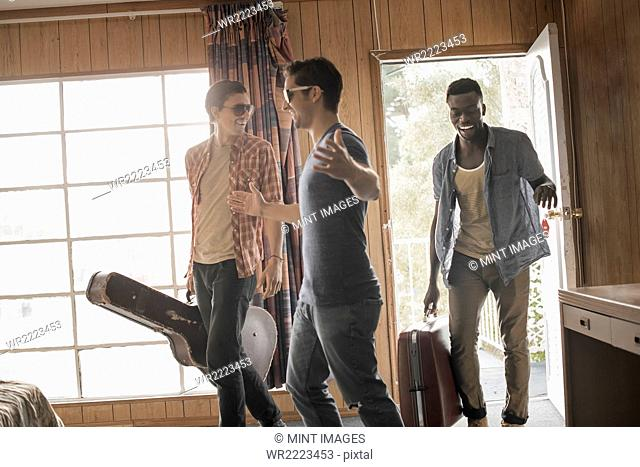 Friends, three young men in a motel room, carrying cases and a guitar