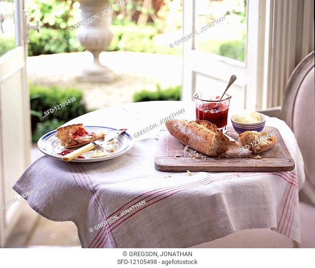 A table set with bread, jam and clotted cream