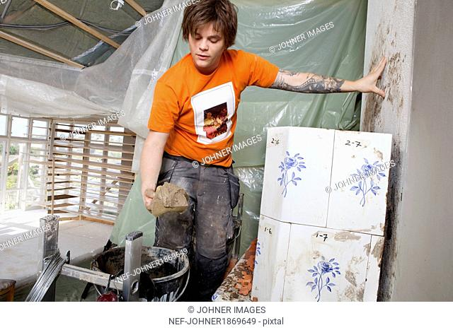 Young man tiling stove