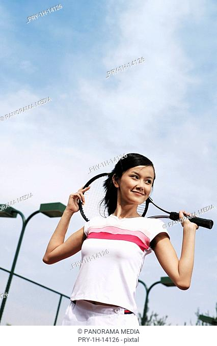 Young woman holding tennis racket, smiling
