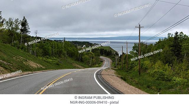 Empty road passing through rural landscape, Grand River, Cape Breton Island, Nova Scotia, Canada