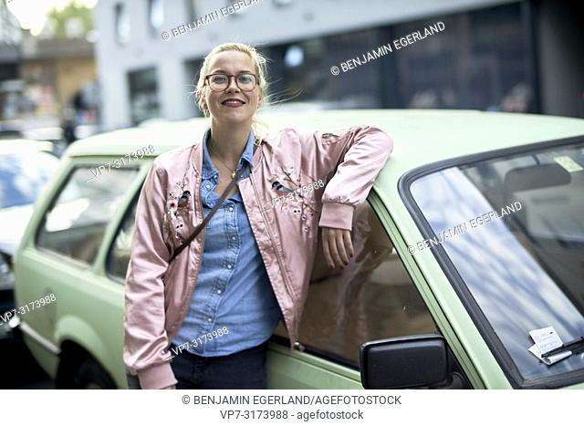 Portrait of woman leaning against vintage car in Berlin, Germany