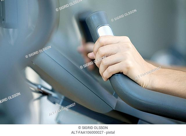 Woman's hands gripping handle of exercise machine, close-up