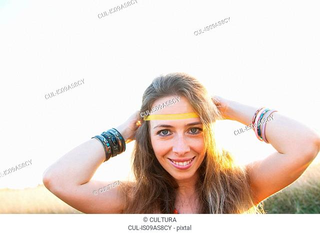 Portrait of mid adult woman, tying hippy headband around head