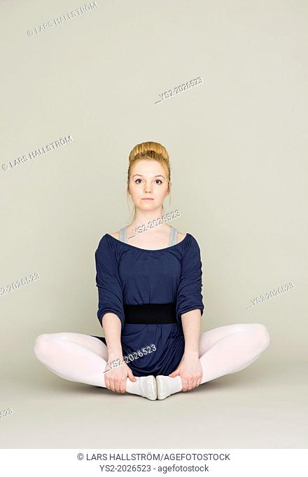 Portrait of serious young blond female teenager in ballet dress
