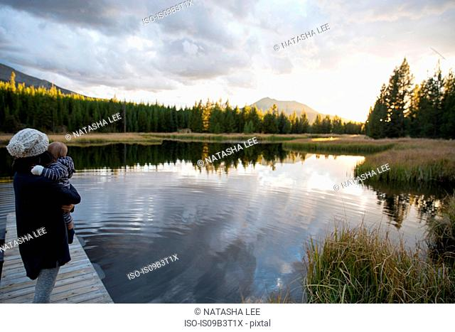 Mother standing on wooden pier beside lake, holding young son