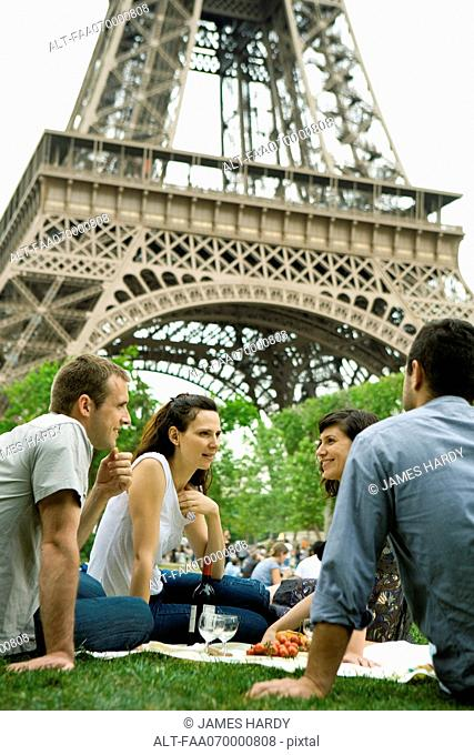 Tourists enjoying picnic at Eiffel Tower, Paris, France
