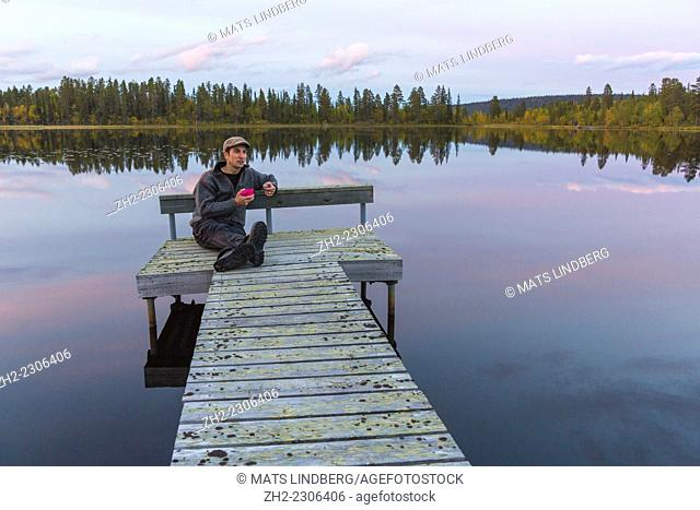 Man sitting on landing stage at a lake in Gällivare, Sweden, drinking coffee