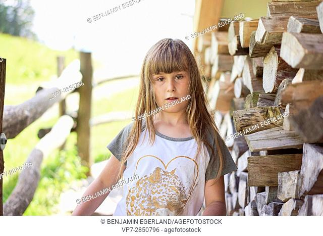 Little serious Bavarian girl next to fire wood