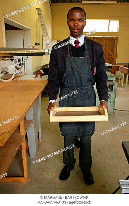 School boy holding wooden breakfast tray he has made in woodwork classroom, St Mark's School, Mbabane, Hhohho, Kingdom of Swaziland