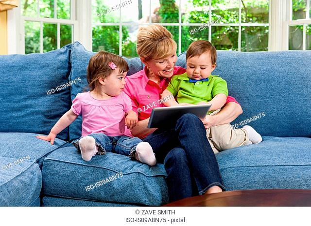 Grandmother and grandchildren on sofa looking at digital tablet