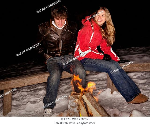 Couple sitting by a fire in the snow