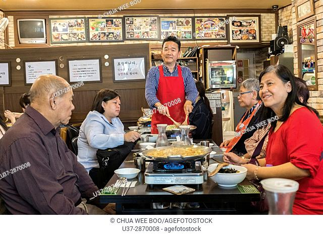 Korean chef serving meals to customers, Seoul, Korea