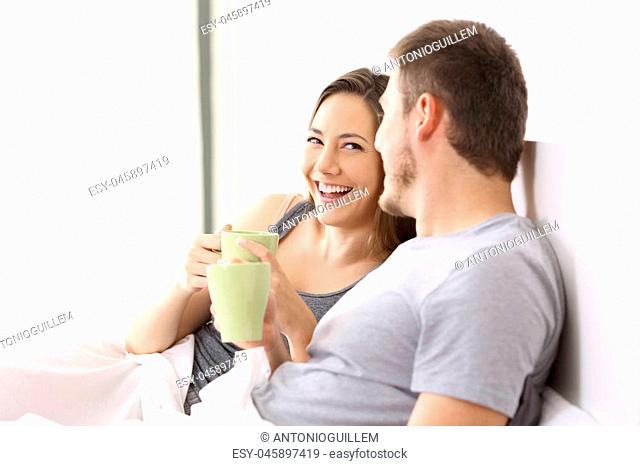 Happy couple having breakfast and talking on a bed of an hotel room or home