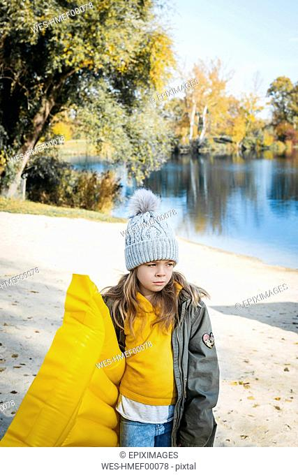Portrait of girl with yellow airbed on the beach in autumn