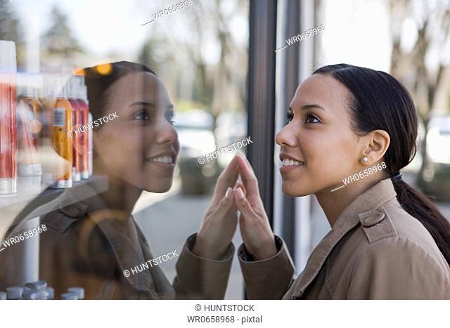 Hispanic woman touching glass window of a salon