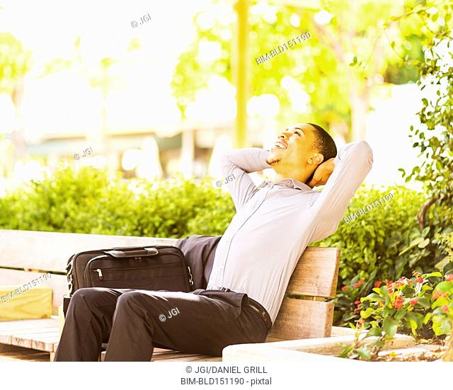 Black businessman relaxing on bench outdoors