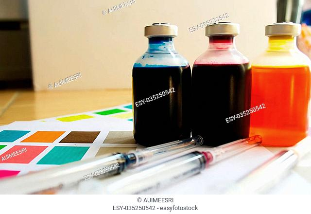 Bottle of ink printer has three colors. Colors is red, yellow and blue with syringe on colored paper