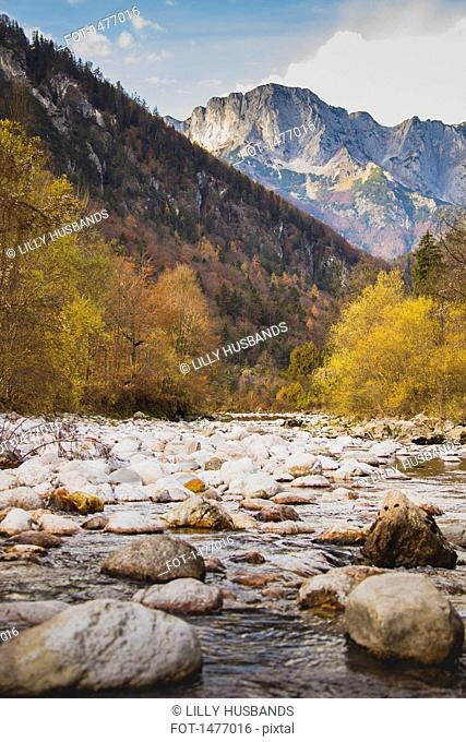 Stones at river against rocky mountains during autumn