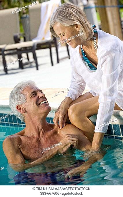 Senior couple enjoying swimming pool