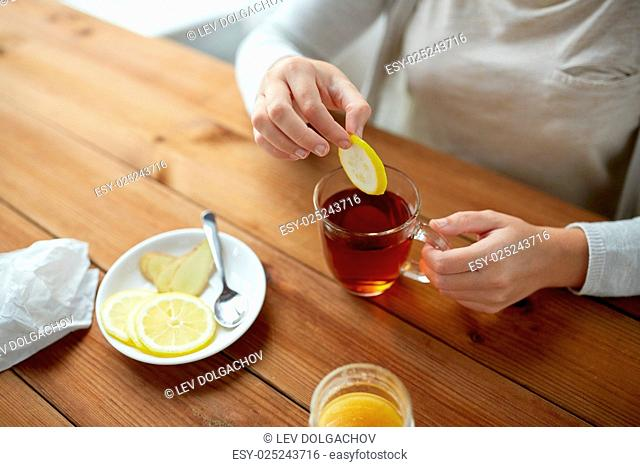 health, traditional medicine and ethnoscience concept - close up of woman adding lemon to tea cup