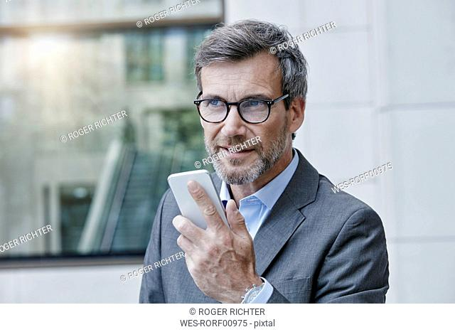 Portrait of businessman speaking voice mails on his smartphone
