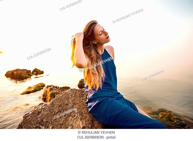 Young woman sitting on beach rock with hand in long hair, Odessa, Ukraine