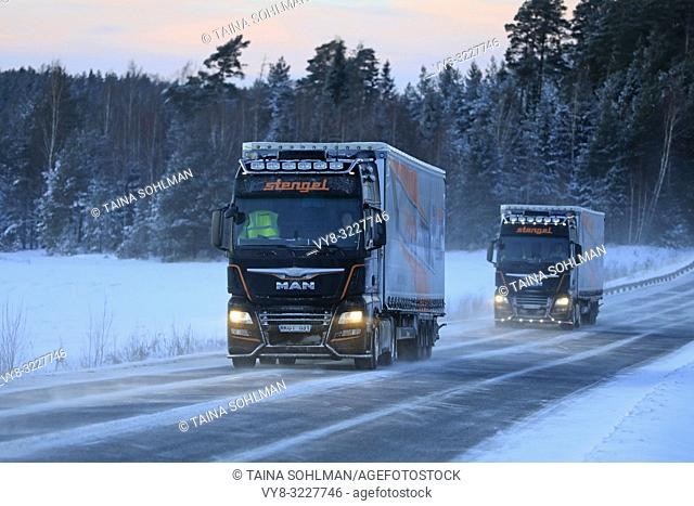 Salo, Finland - January 18, 2019: Two Customised MAN semi trailer trucks of Stengel LT haul goods through winter scenery at dusk in South of Finland