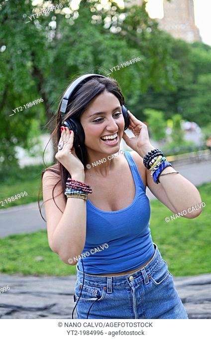 Attractive young mixed race woman listening to music in Central Park, New York City
