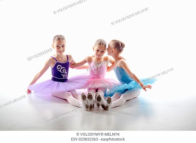 Three little ballet girls sitting in multicolored tutus and pointe shoes together on white background