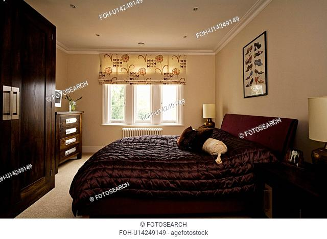 Black quilt and patterned blind in cream bedroom