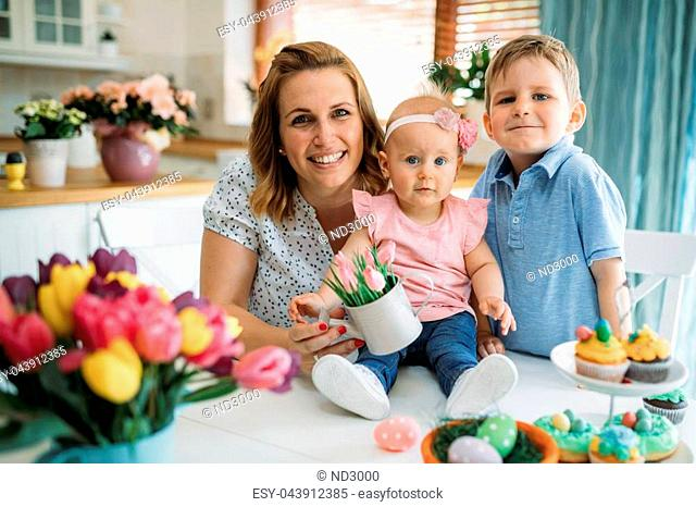 Happy easter. A mother and her kids painting Easter eggs. Happy family preparing for Easter