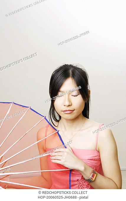 Close-up of a young woman holding a parasol with her eyes closed