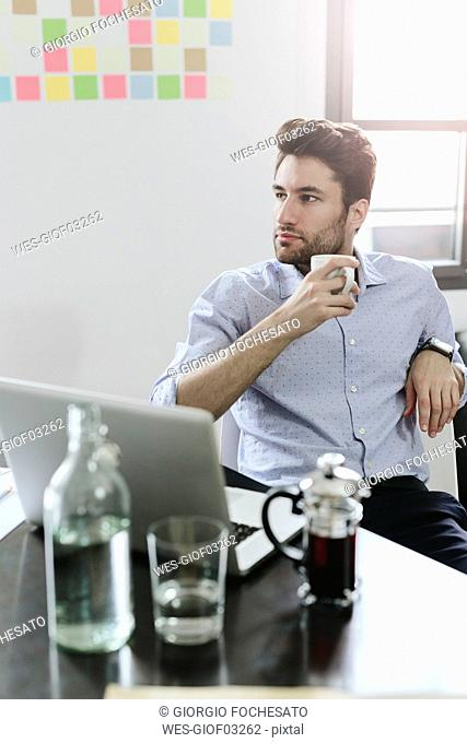 Young businessman sitting at desk with pot of coffee