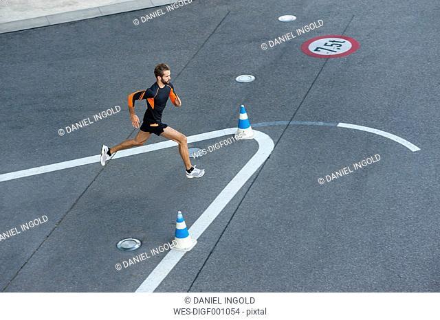 Man running on street with markings