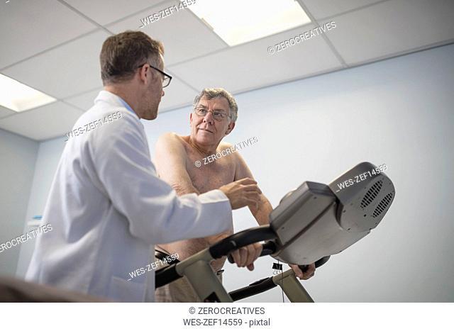 Doctor talking to senior patient on treadmill