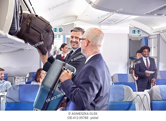 Businessmen loading luggage into storage compartment on airplane
