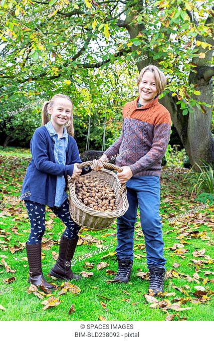 Caucasian brother and sister posing with basket of nuts