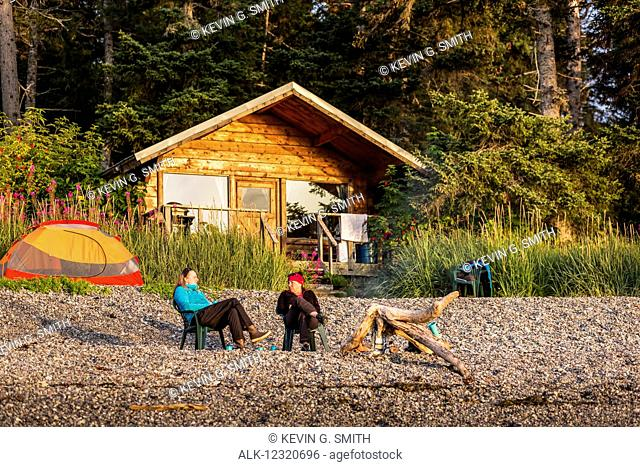 Two women relaxing in chairs on the shore of Hesketh Island with a public use cabin in the background, Southcentral Alaska, USA