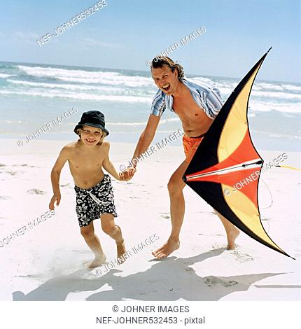 Father and a son playing with a kite on the beach, Sweden