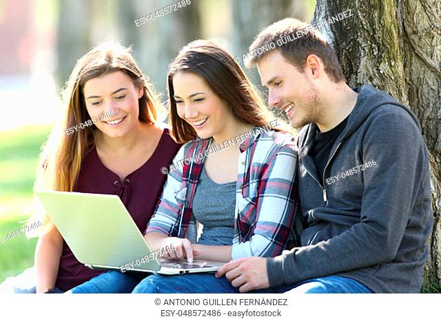 Three happy teenagers searching media content together on line with a laptop sitting on the grass in a park