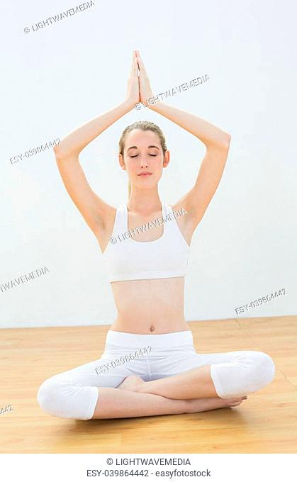 Concentrating calm woman meditating sitting in lotus position with hands raised in prayer with eyes closed
