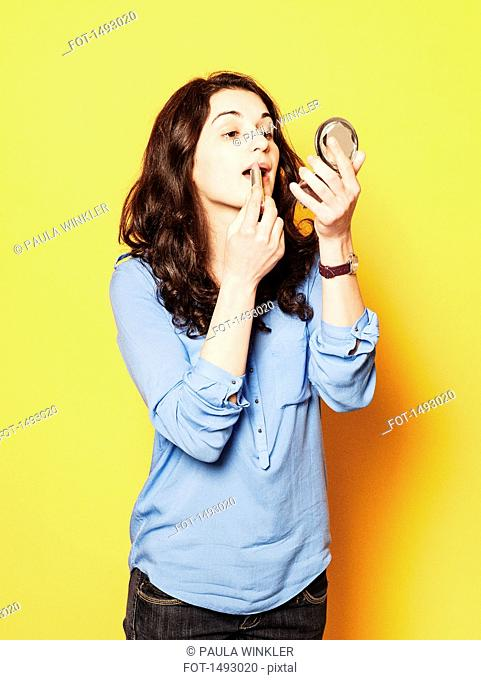 Young woman applying lipstick against yellow background