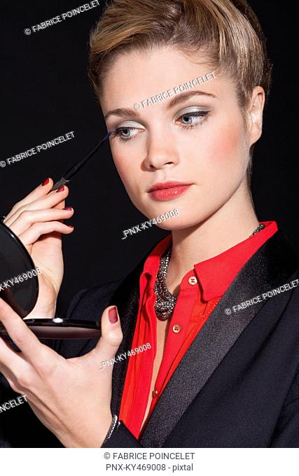 Beautiful woman applying eyeliner