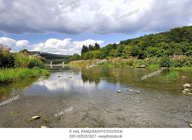 landscape of river flowing near the little village, crystal water and flowering banks, shot in bright summer light and reflecting white cumulus clouds
