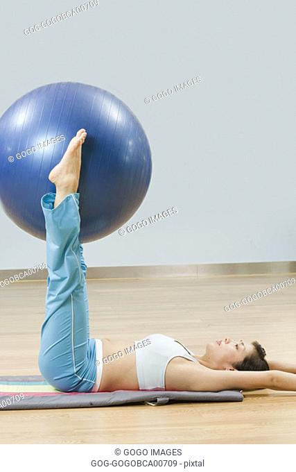 Young woman holding an exercise ball between her ankles