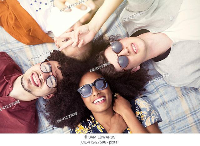 Overhead portrait smiling friends laying in circle on blanket